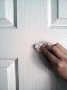 Kat's hand as she cleans the door with rubbing alcohol